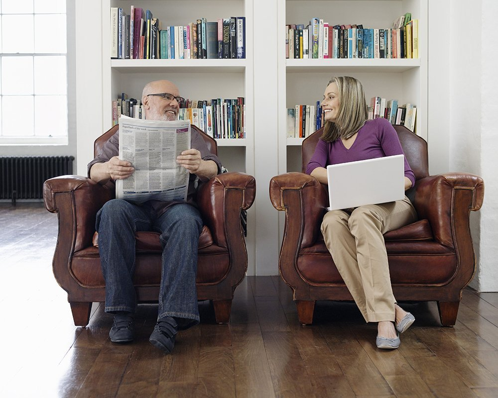 Full length of a middle aged couple sitting in armchairs with newspaper and laptop at home